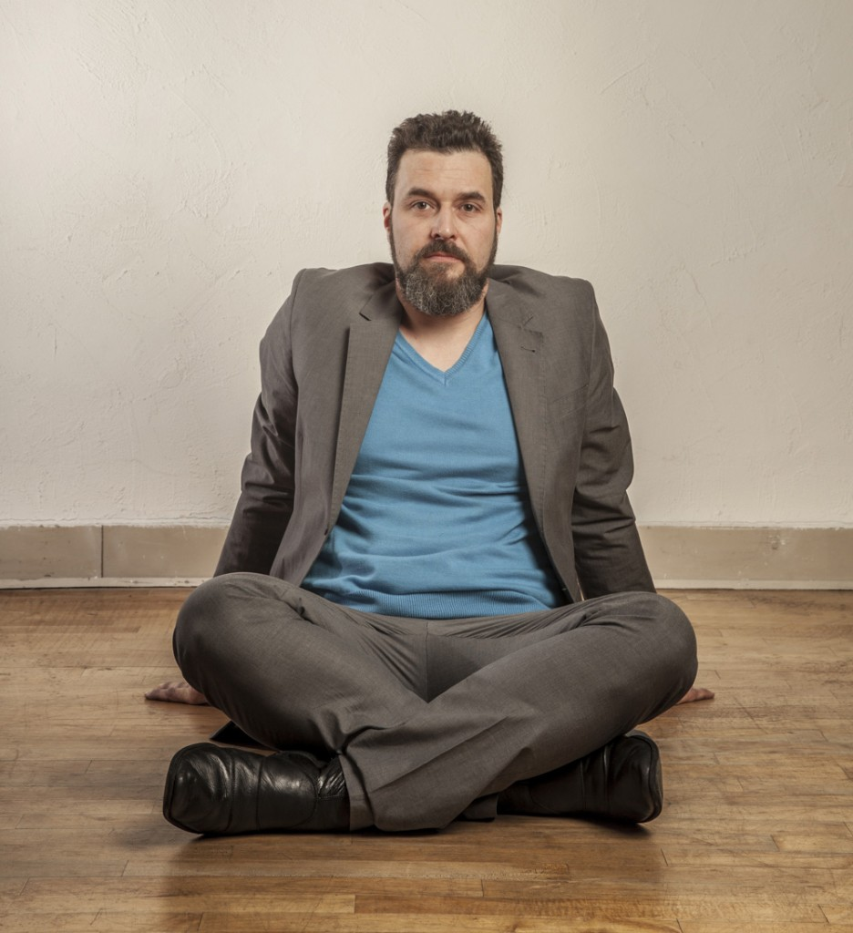 Business man with beard, sitting on wooden floor.